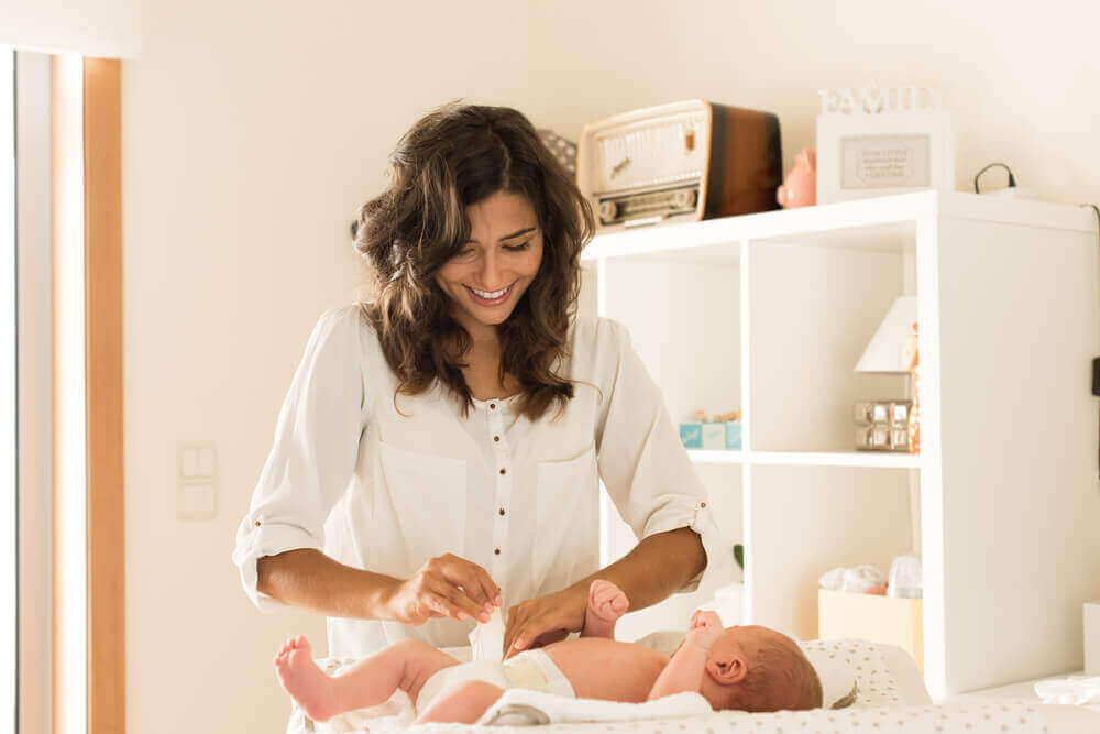 äiti vaihtaa vauvan vaippaa
