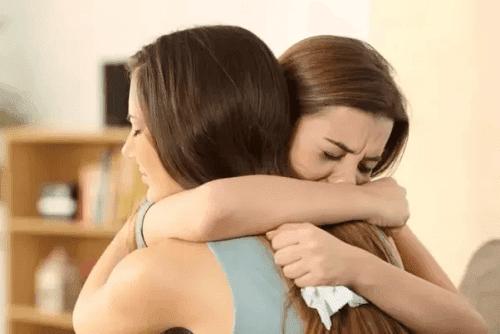 ystävät itkevät ja halaavat