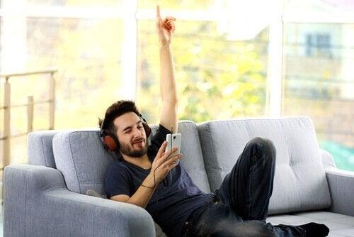 mies kuuntelee musiikkia sohvalla
