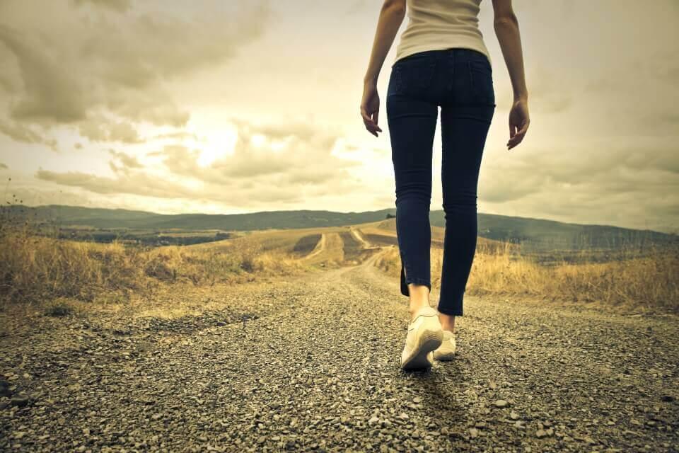 nainen kävelemässä yksin pitkällä tiellä