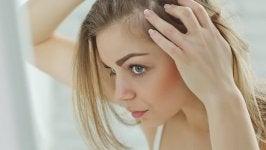 nainen tarkastelee hiuksiaan