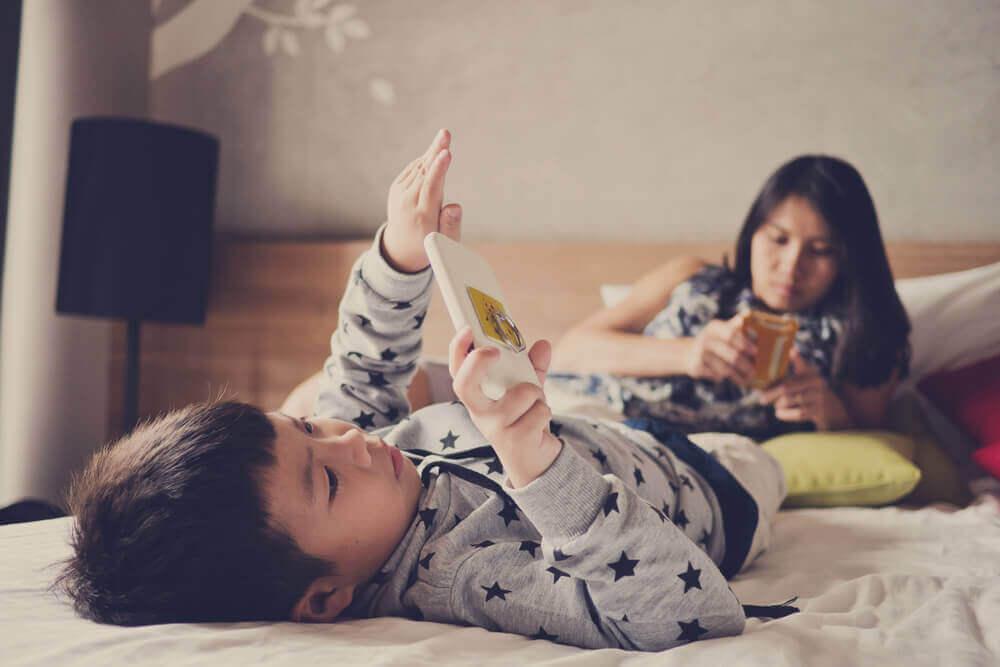 poika ja äiti räpläävät puhelimia