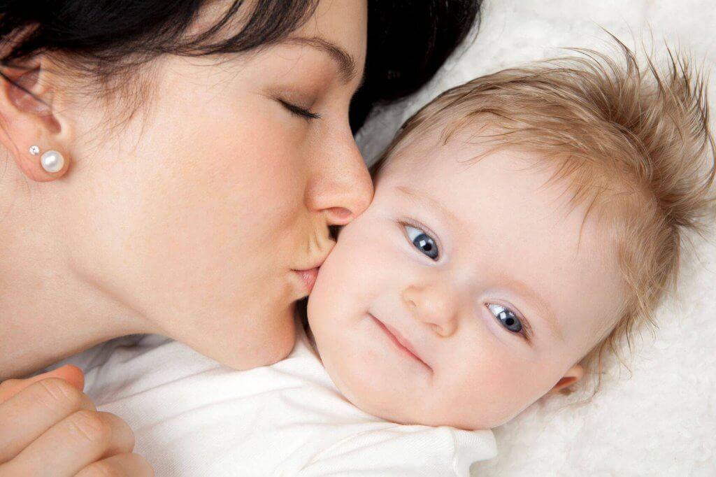 äiti antaa vauvalleen suukon