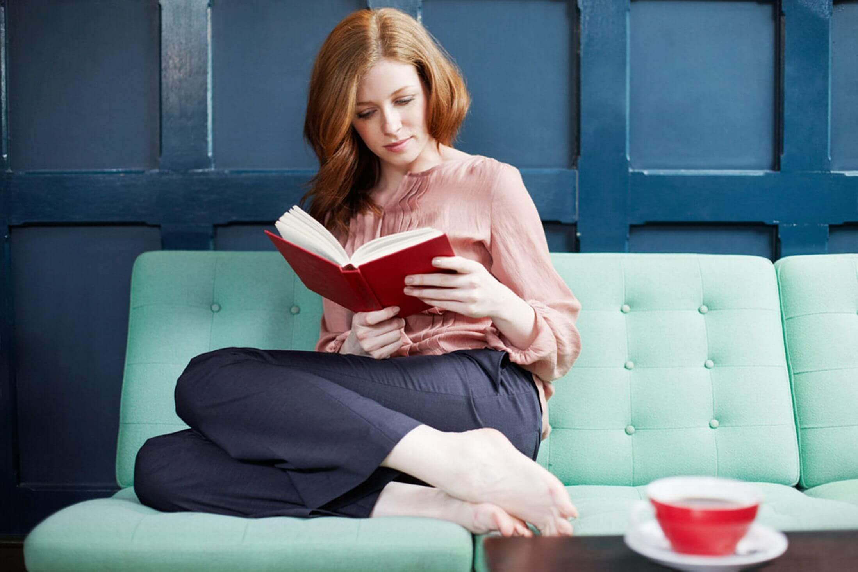 nainen lukee sohvalla