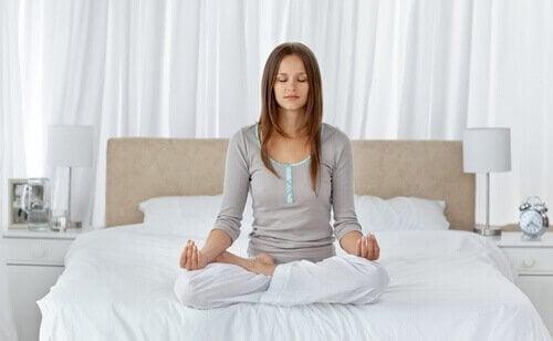 nainen meditoi sängyllä
