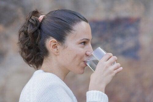 nainen juo vettä hoitaakseen huuliaan