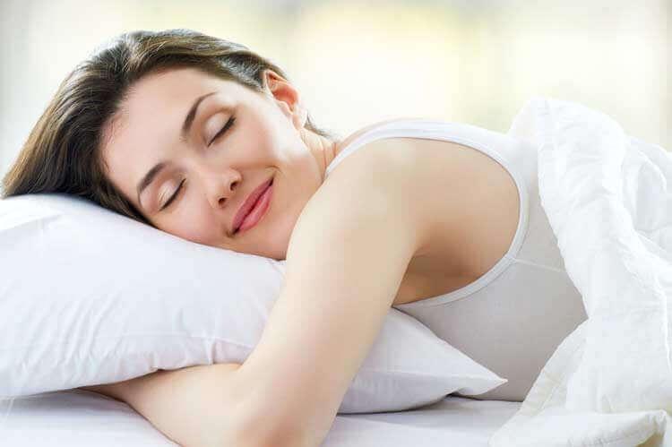 hymyilevä nainen sängyssä