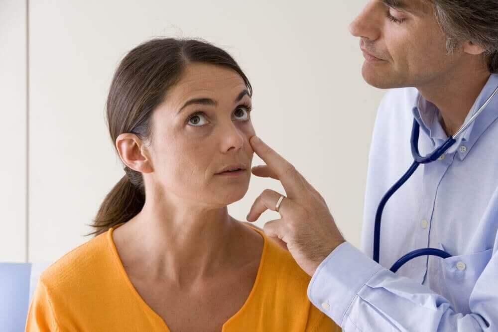 lääkäri tarkastaa naisen silmät
