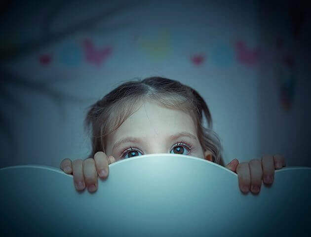 tyttö kurkistaa sängystään