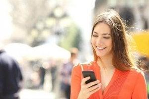 nainen katselee puhelintaan