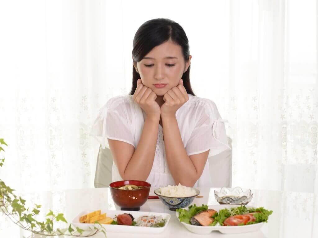 nainen miettii, kuinka monta ateriaa päivässä hänen kannattaisi syödä