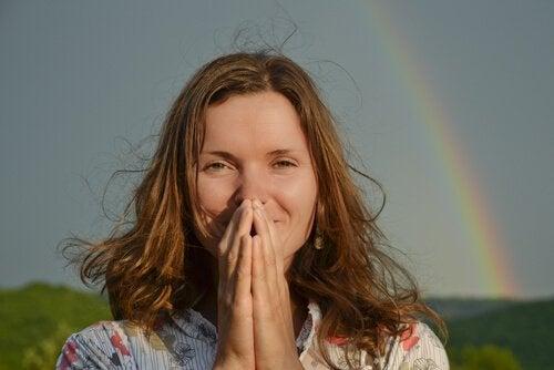 iloinen nainen ja sateenkaari