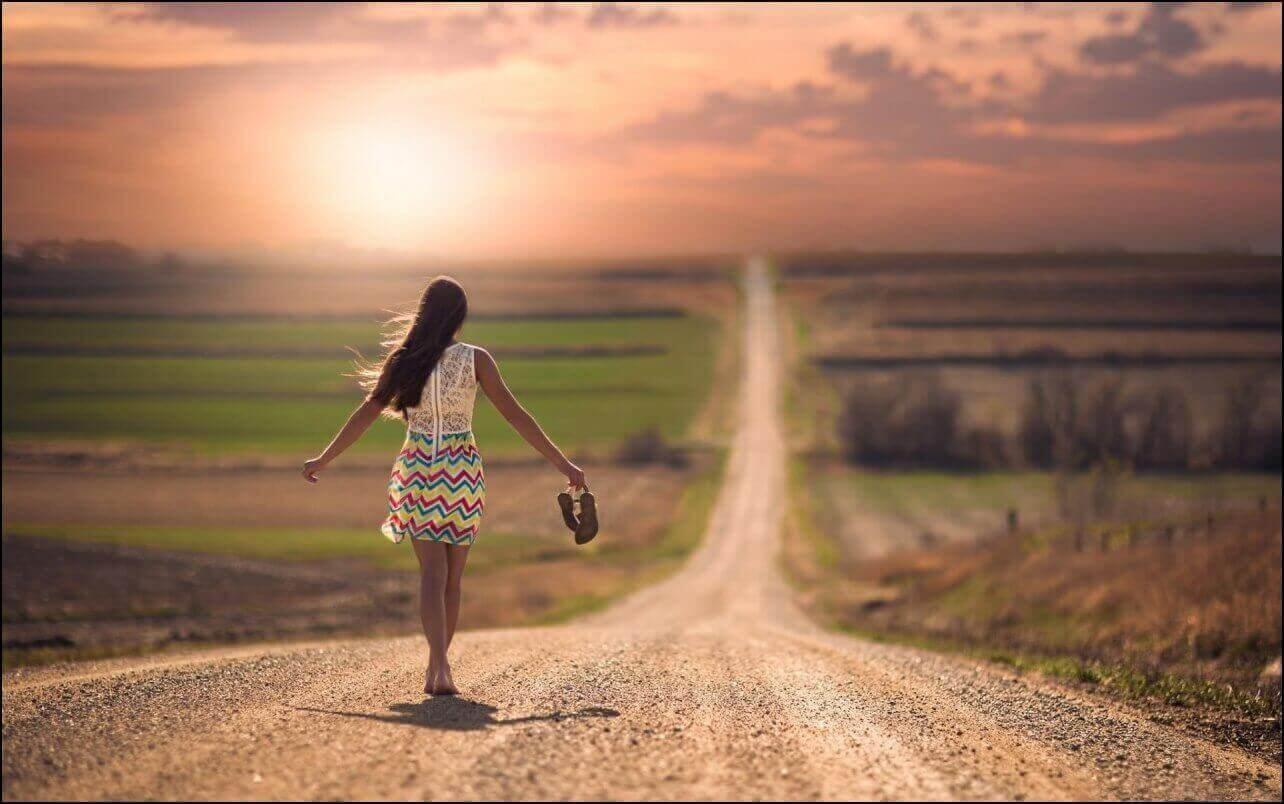 nainen kävelee tiellä paljain jaloin
