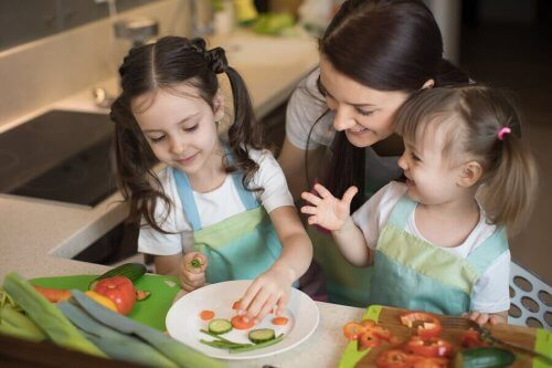 äiti ja tytöt laittavat ruokaa
