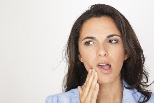 nainen kaipaa hoitoa leukakivun lievittämiseen