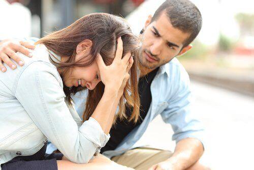 mies lohduttaa itkevää naista