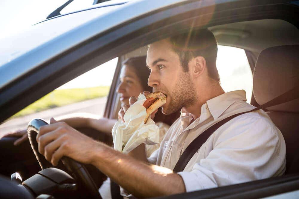 Mies syö ajaessaan.