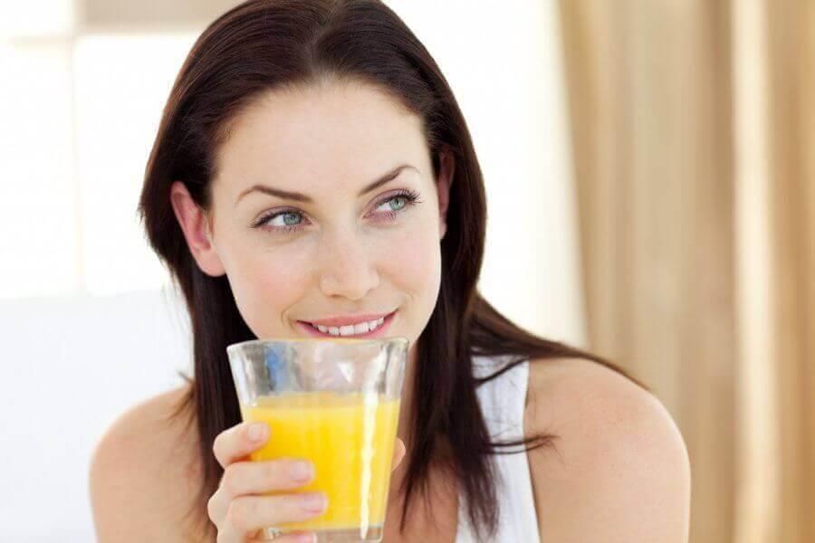 Nainen juo ananasmehua.
