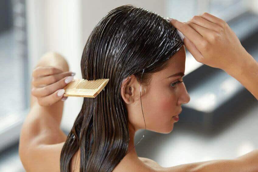 Nainen kampaa hiuksiaan.