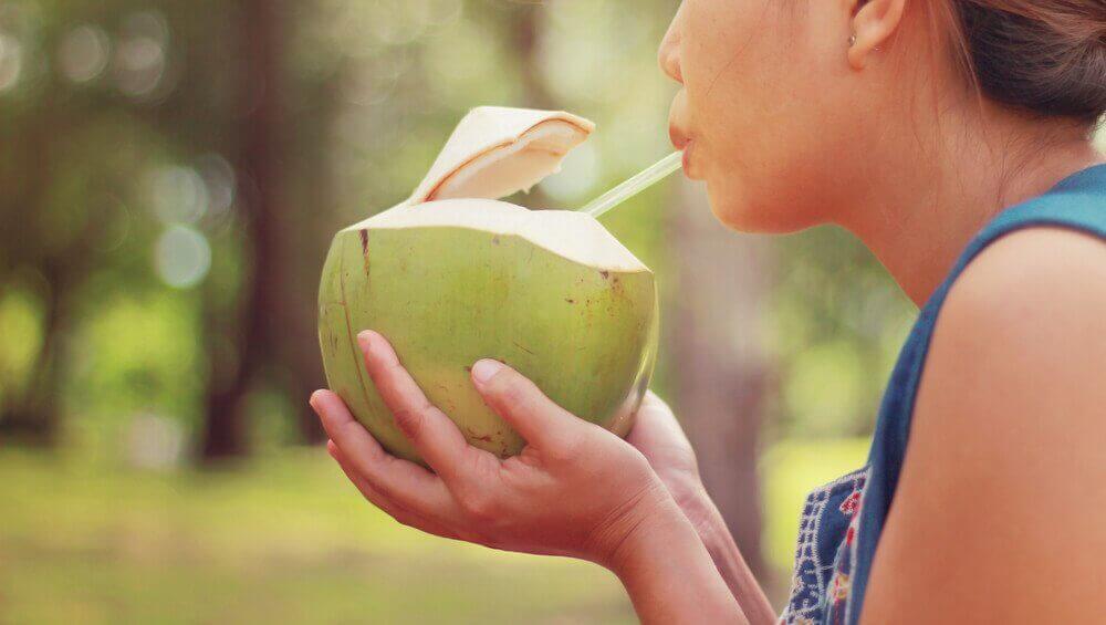 Nainen juo kookosvettä suoraan kookoksesta.