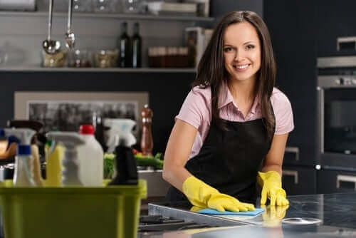 Iloinen nainen siivoaa keittiötä