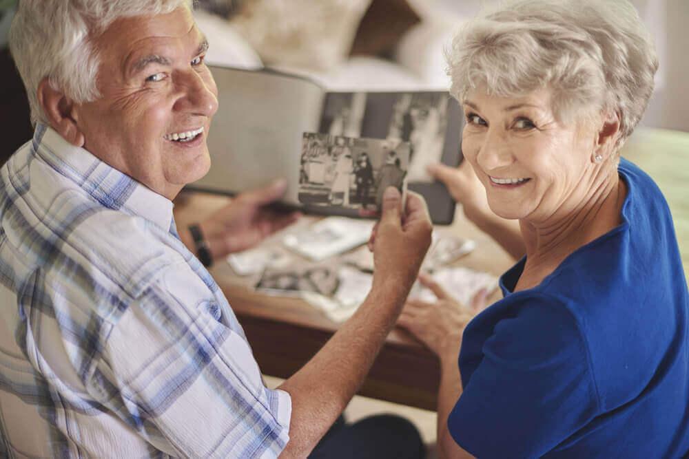 Vanha pari katselee valokuvia.