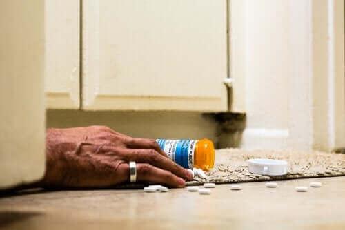 Kaatunut pilleripurkki ja käsi vessan lattialla.