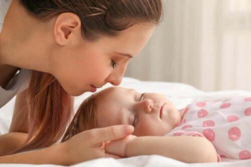 Vauva nukkuu ja äiti on vierellä.