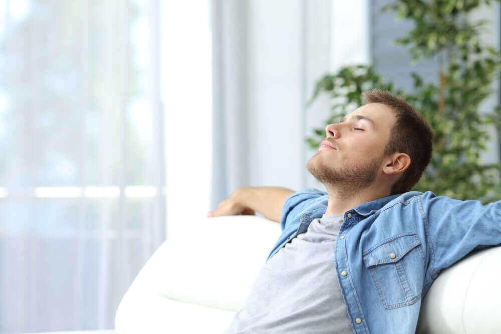 Mies rentoutuu sohvalla.