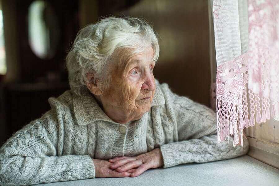 Vanhus katselee ikkunasta ulos.